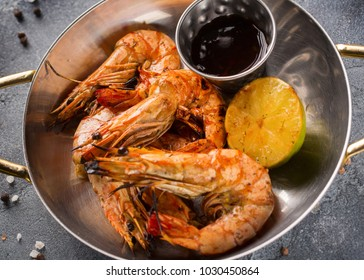 Prawns roasted on frying grill pan with lemon and sauce on dark background