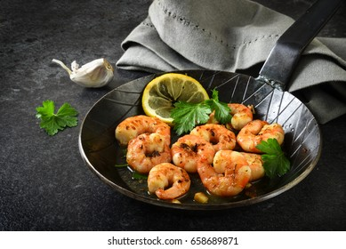 prawns shrimps with garlic, lemon, spices and italian parsley garnish in a black pan on a dark slate plate, selected focus, narrow depth of field
