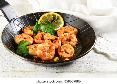 prawns shrimps with garlic, lemon, spices and italian parsley garnish in a black pan on white painted rustic wood, selected focus, narrow depth of field