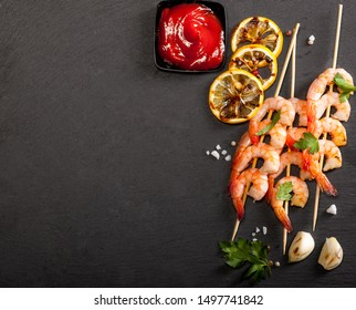 Prawns Shrimps with lemon, garlic and herbs on black stone background. Top view with copy space.