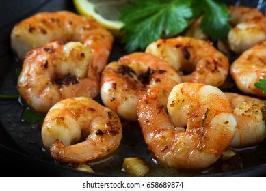 prawns shrimps roasted in a black pan with garlic, lemon, spices  and italian parsley garnish, close up, selected focus, narrow depth of field