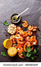 Prawns Shrimps roasted and served on stone slate with lemon, garlic and green sauce