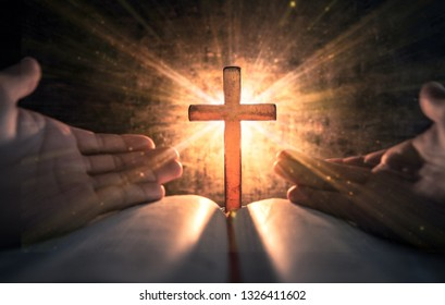 Pray hands with light the cross on bible in worship room. christian praying concept.