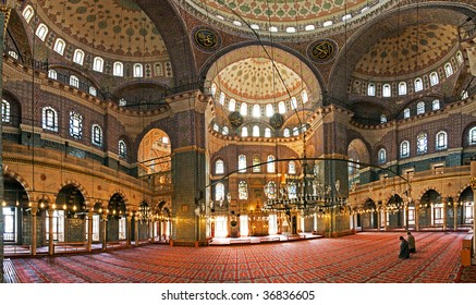Pray - panoramic view in the interior of a mosque with two people praying