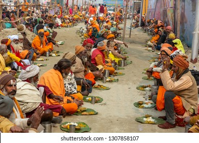 Prayagraj (formerly Allahabad), India - January 13, 2019: Sadhus eating the food offered by devotees as a donation or charity during  Kumbh Mela, 2019, Prayagraj. It is open to everyone.