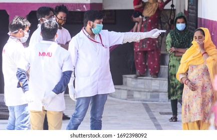 Prayagraj: Medics check the temperature of attendees of a religious congregation of in Delhi's Nizamuddin area during their isolation period at a COVID 19 quarantine facility in Prayagraj on Friday, A