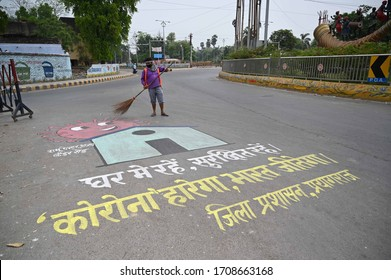 Prayagraj: A municipal corporation worker clean a road as graffiti of slogan seen on road during a nationwide lockdown in prevent measure of COVID 19 Coronavirus in Prayagraj.