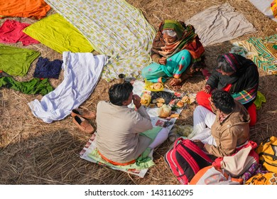 Prayagraj,10, February, 2019 :Top view of rural family eating home food after  holy bath near their clothes drying  on ground at Sangam in Kumbh Mela, Praygraj, Uttar Pradesh, India,