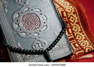prayer beads encircling the Koran over the prayer mat and red carpet