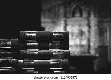 Prayer books and blurry altar at background. Religion concept. Selective focus. Black and white photo.