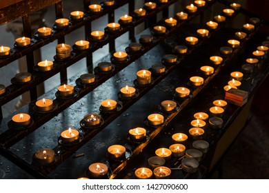 Prayer candles burning in rows in church