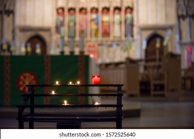 Prayer candles lit inside a church as a votive offering in an act or prayer