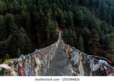 Prayer flags and cloth tied to a suspension bridge in the Himalayan mountains of Nepal surrounded by beautiful pine forests and pristine rivers