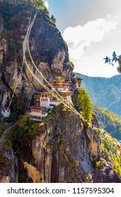 Prayer flags and a view of the Tiger's Nest monastery also known as the Paro Taktsang