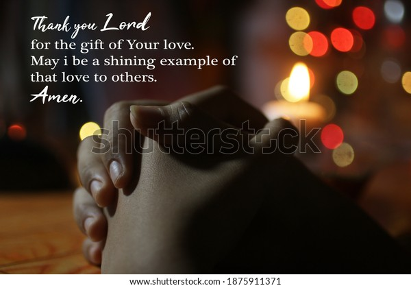 Prayer hands on the table with candle and colorful Christmas lights background. Thank you Lord for the gift of Your love. May i be a shining example of that love to others. Amen. Prayer quote concept.