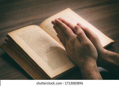 Prayer, man hands over an open book Holy Bible, wooden desk background. Faith, religion gospel and spirituality concept