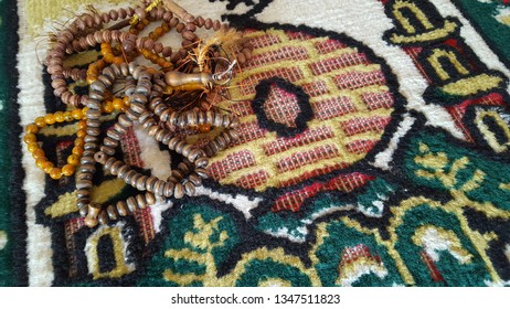 Prayer rug in the mosque with prayer beads on it
