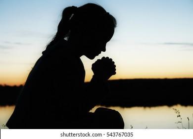 Prayer. Silhouette girl prays at sunset.