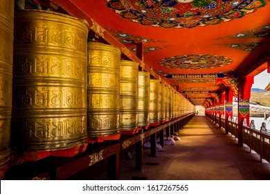 Prayer wheels lining the long corridor of a tibetan temple structure