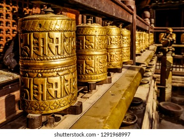 A prayer wheels on a spindle made from metal and wood. Mantra Om Mani Padme Hum is written in Newari language of Nepal on the outside of the wheels. Golden Temple (Kwa Bahal) buddhist temple in Patan