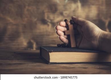 prayer woman holding cross on Bible