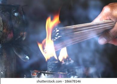 Prayers burning incense sticks on a temple fire