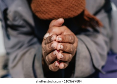 Praying beggar woman kneeing covering her face with kerchief and clutches her hands close up image
