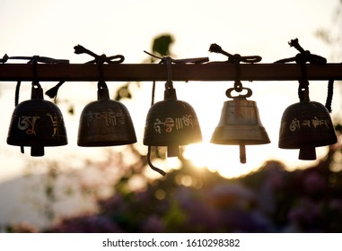 Praying bells hanging outdoor in Kathmandu, Nepal. Famous Buddhism praying mantra 'Om Mani Padme Hum' are carved on them. This mantra is believed to get rid of the impurities in body, speech, and mind