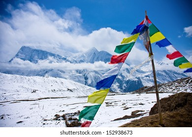 praying flags floating in the wind in front of the annapurnas, nepal / Himalaya Range praying flags