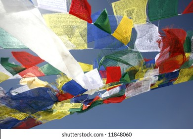 praying flags floating in the wind on blue sky
