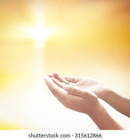 Praying God concept: Prayer open empty hands with palm up over blurred cross with golden light background.