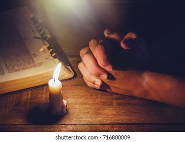 praying hand  and blurred open bible on wooden table with candle light and the light from above, trust concept , Christian background with copy space for your text
