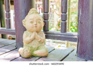 "praying hand or "" Sawatdee"" hands sign or traditional of Thai greeting referred to as the ""wai"", child clay thailand on wooden floor"