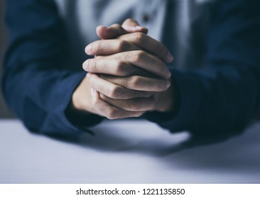 Praying hands against dark background.