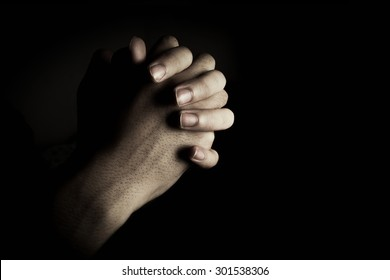 Praying hands is in the dark with light on the hands.