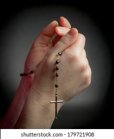 Praying Hands holding rosary beads on black background