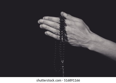Praying hands holding rosary with the cross