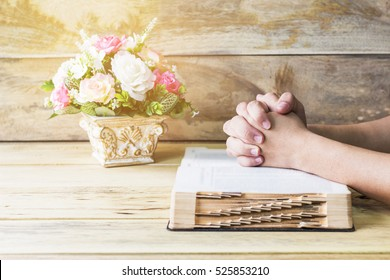 praying hands of the man on burred page of and old bible over wooden table background