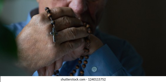Praying hands of an old man holding rosary beads.