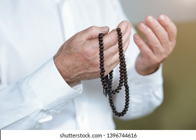 Praying hands of an old man with rosary beads