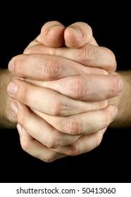 Praying hands on black background