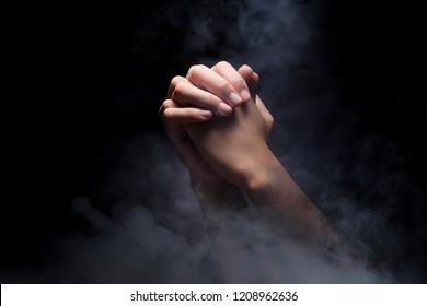 Praying hands over dark background. Christian Pray