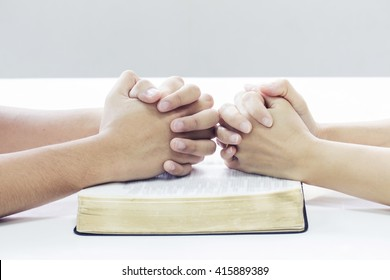 praying hands of two people on one bible on white table background