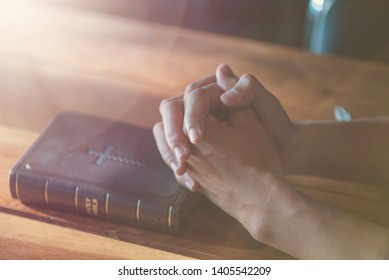 Praying hands of young man with Bible , pray to God and  hoping for better,success, forgiveness. Power of religion, belief, worship.Bible and christian study concept