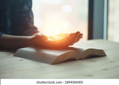 mains de prière, jeune femme priant les mains ensemble sur la Sainte Bible, lumière spirituelle, paix de l'esprit et de l'âme