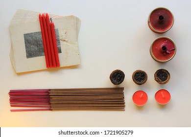 Praying items for Buddha and Taoist Deities. Joss, Paper, candle and smoke. Hungry ghost festival praying ceremony. Flat lay. Copy space. Religion concept. On the white background.