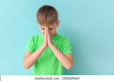 Praying little boy on color background
