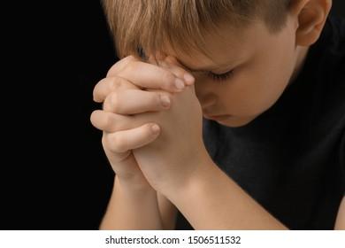 Praying little boy on dark background, closeup