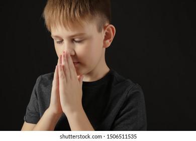 Praying little boy on dark background
