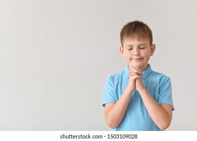 Praying little boy on light background